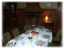 Large dining table and chairs, open fire, Christmas garlands and lights